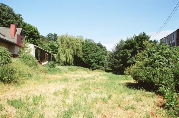 """Teren przyszłego """"ogrodu wiejskiego"""" - przed rozpoczęciem prac rewitalizacyjnych; po lewej na wyniesieniu - budynek ptaszarni"""