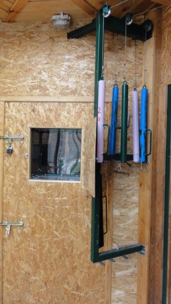 Widok fragmentu zaplecza po stronie obsługi, w środku sześcienne okienko wglądu pracowników do boksu zwierząt